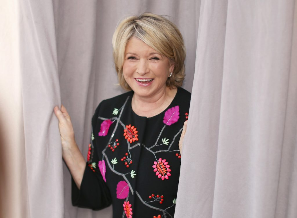 Martha Stewart smiles and holds some curtains