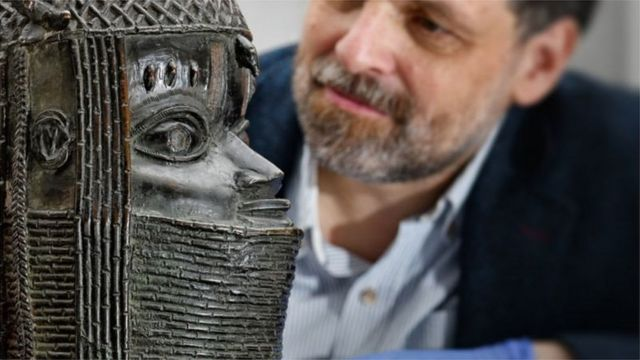 Neil Curtis, Head of Museums and Special Collections, dey wit a Benin Bronze wey dey rep di Oba of Benin für di University of Aberdeen in Schottland
